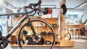 Vorderrad eines Fahrrad und im Hintergrund Auslage mit Fahrradzubehörartikel