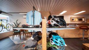 Helm und Kapuzenauslage mit Kleiderstange im Ausstellungsraum eines Fahrradgeschäftes